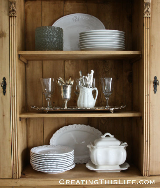 hutch with white dishes and silver