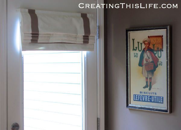 Roman shade and framed poster as kitchen decor at CreatingThisLife.com