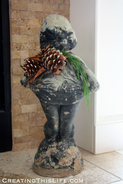 Statue with greenery and pinecones