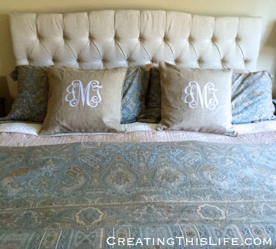 Upholstered headboard and monogrammed pillows