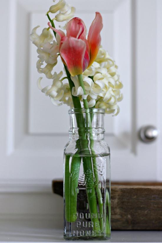 Hyacinth and tulip in vintage honey jar